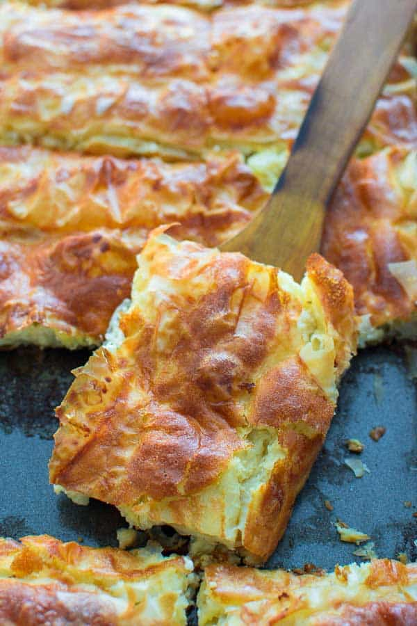 "This delicious Bulgarian Feta Pie ""Banitsa"" is a true gem of Balkan cuisine. Made with layers of filo dough, crumbled feta, and eggs, it makes a perfect breakfast or mid-day snack."