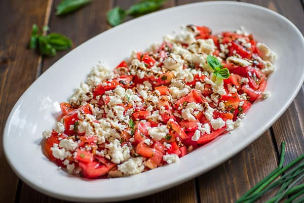 This simple Tomato Feta Salad is one of the best, easiest salads you'll make! Fresh herbs, succulent tomatoes, creamy feta cheese and a touch of balsamic reduction.