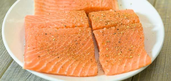 seasoning salmon with salt, pepper, and Cajun seasoning