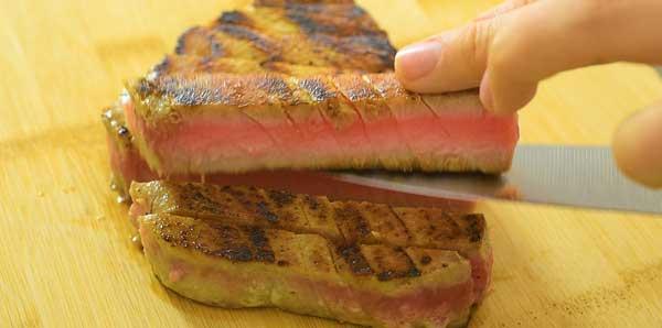 cutting ahi tuna steak on wooden board