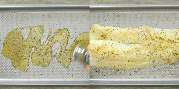 seasoning cod fish on a baking tray