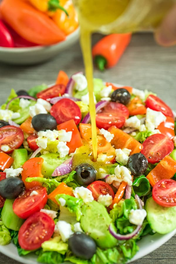 Greek Salad Dressing is being poured over Greek Salad
