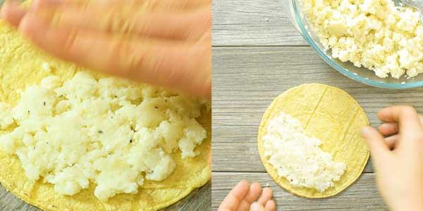 putting potato filling on a corn tortilla