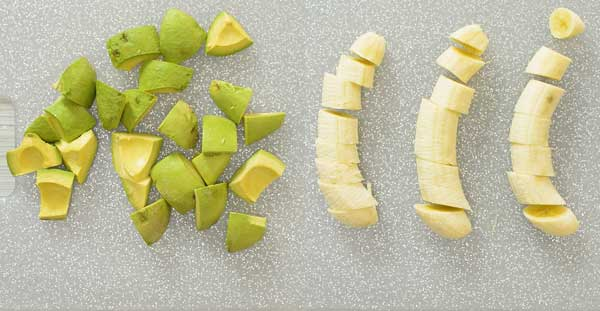 Chopped avocados and bananas on a cutting board