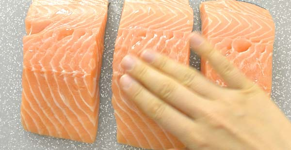 rubbing oil onto the salmon fillets