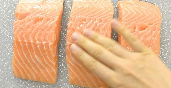 rubbing oil onto the salmon fillets