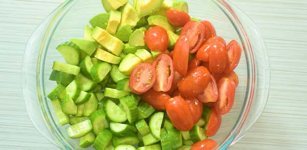 chopped cucumbers, avocados, and tomatoes in a bowl