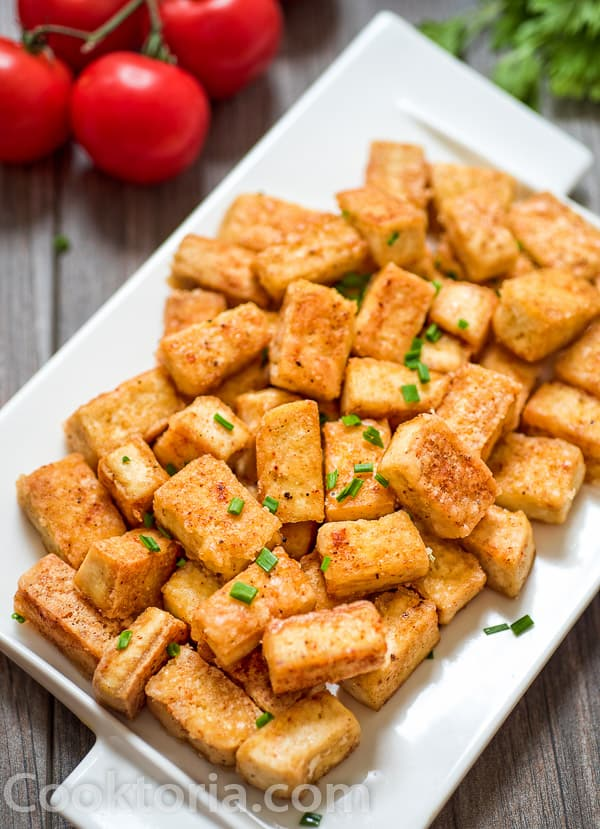 Fried Tofu on a plate with Tomatoes on background