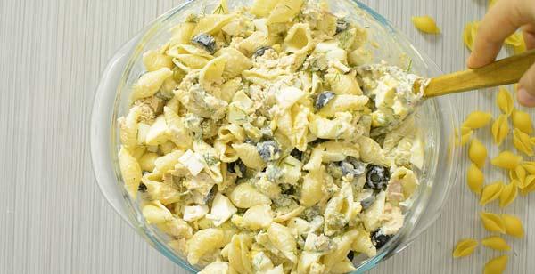 mixing tuna pasta salad in a bowl