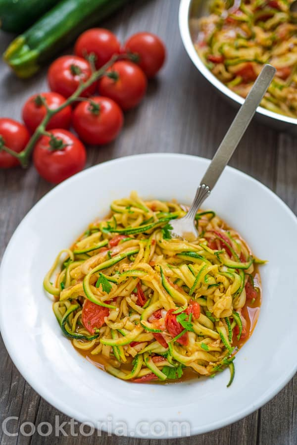 Zucchini Noodles on a plate with vegetables on a background