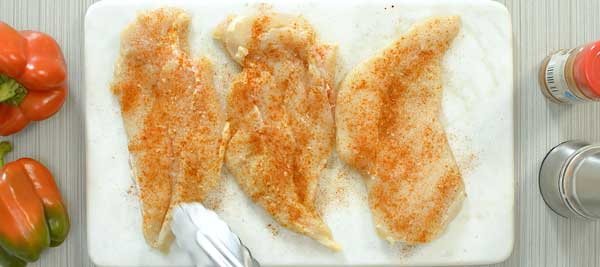 seasoning chicken with paprika and salt