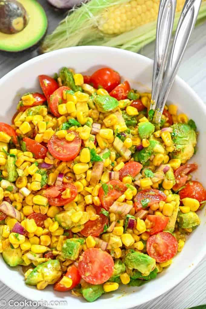 Avocado Corn Salad in a bowl with vegetables on the background