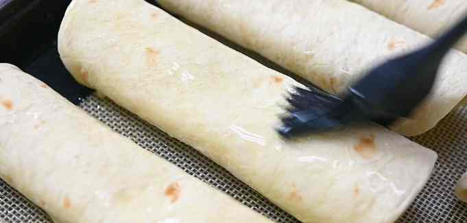 brushing the taquitos with oil