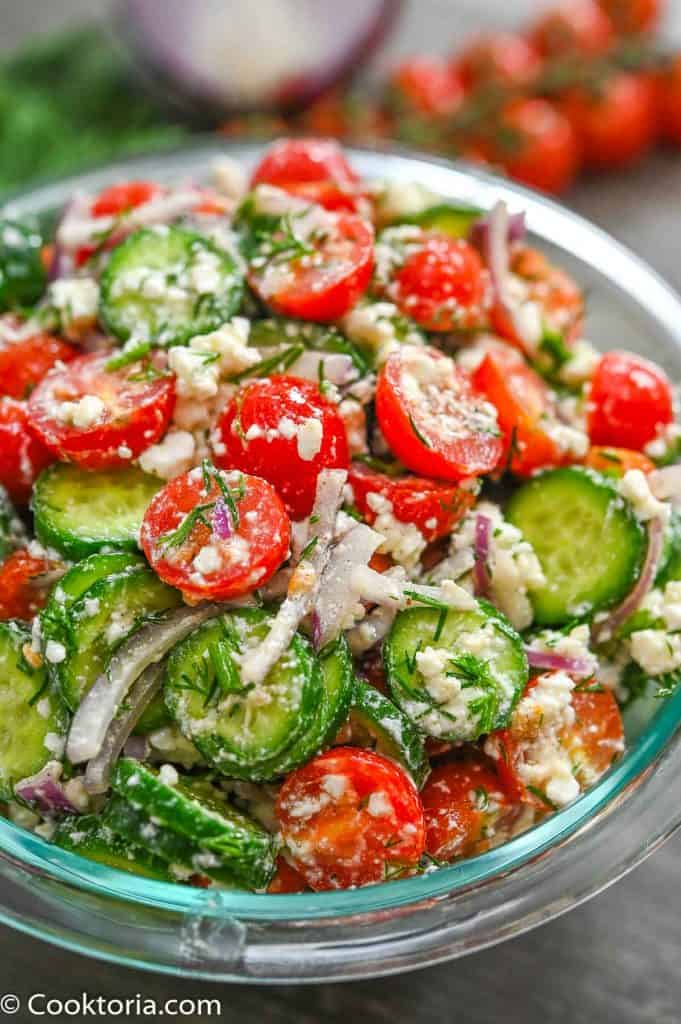 Cucumber Tomato Feta Salad with vegetables on the background