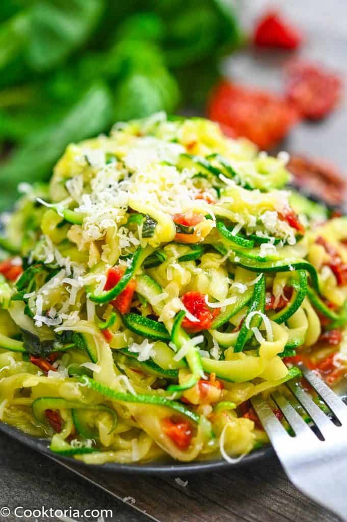 Zucchini noodles on a plate sprinkled with parmesan