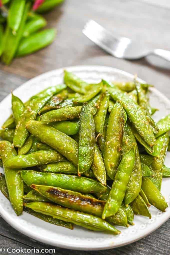 Roasted Sugar Snap Peas on a plate with veggies on the background